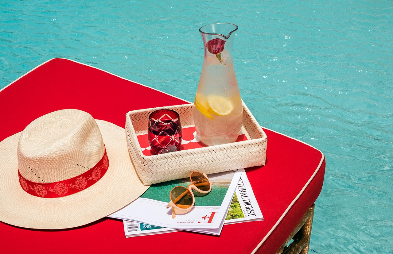 table next to pool with lemonade and a hat