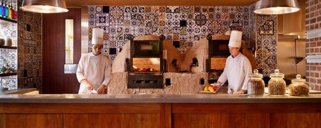 two chefs in kitchen in front of wood fired ovens