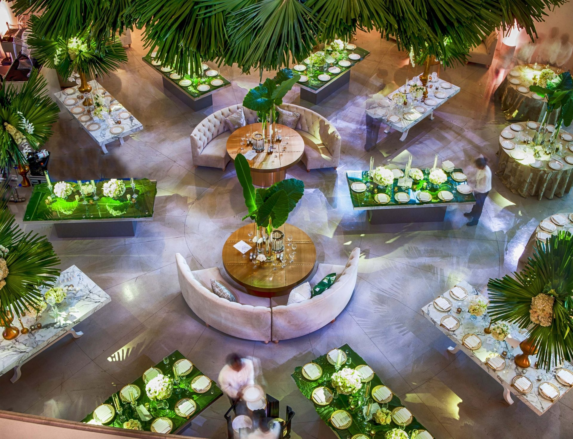 looking down on tables set up for dining with a lot of palm leaves as decoration