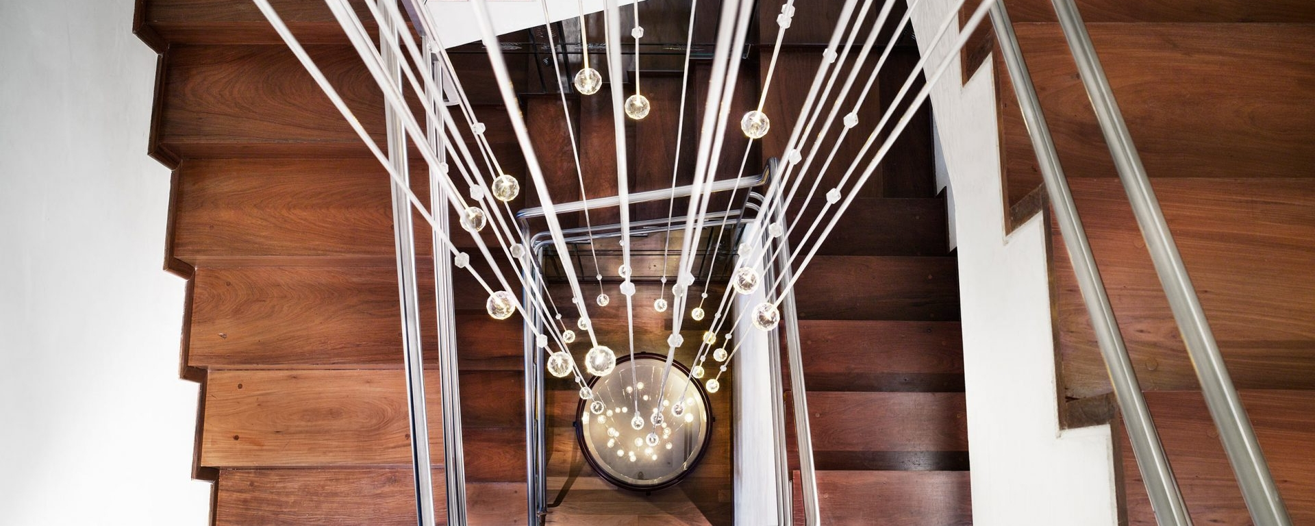 looking down a staircase with hanging lightbulbs