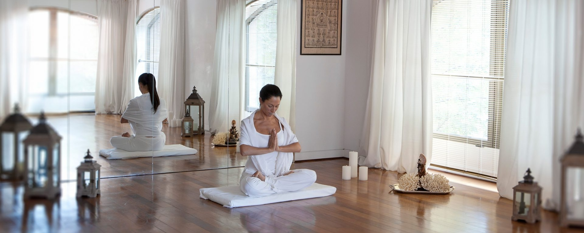 women sit on wood floor in yoga positions