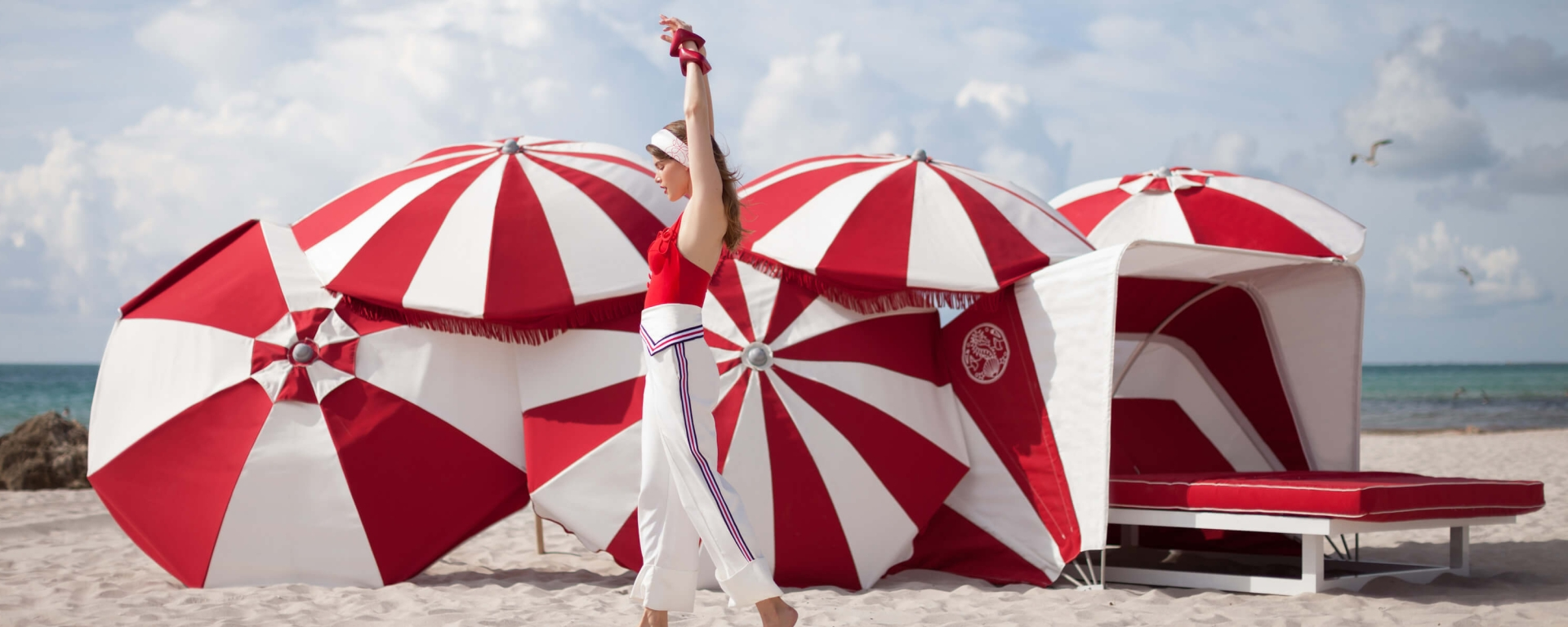 woman walking on the beach in front of red and white umbrellas