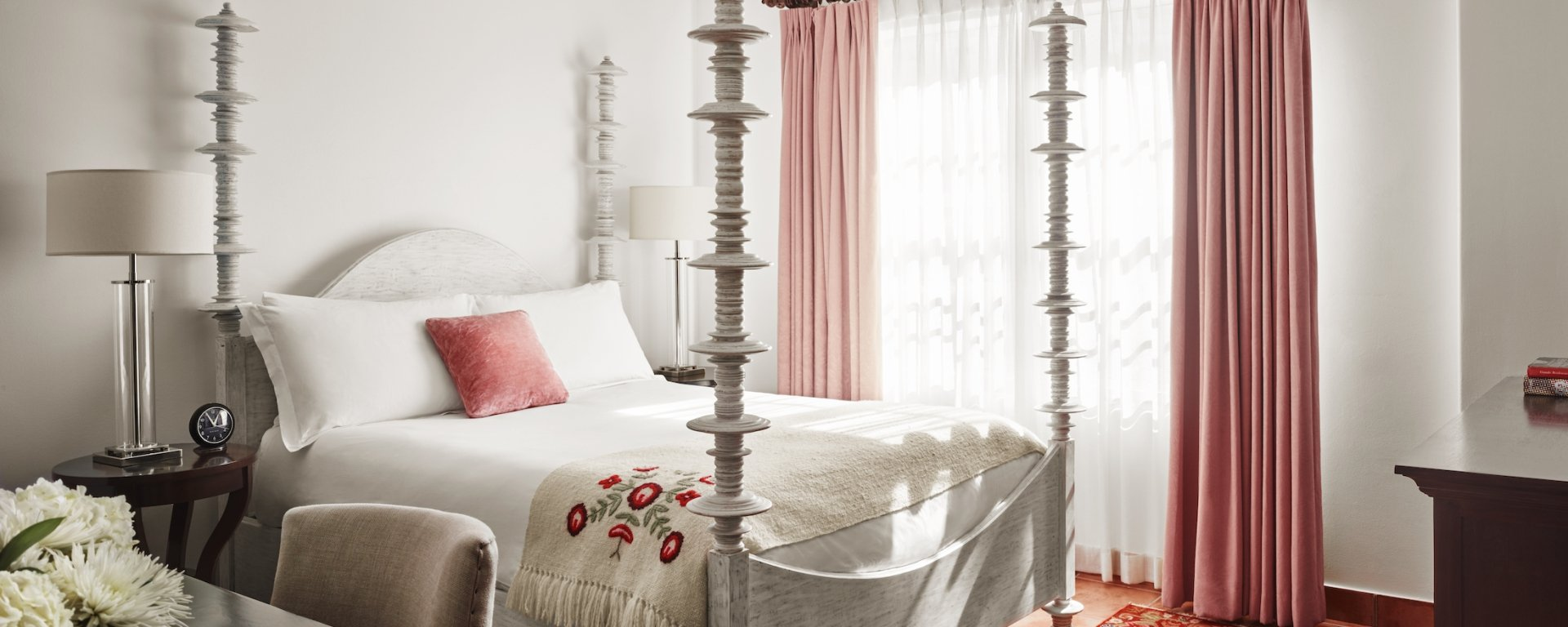 queen bed with four posts and pink curtained windows and red and gold carpet