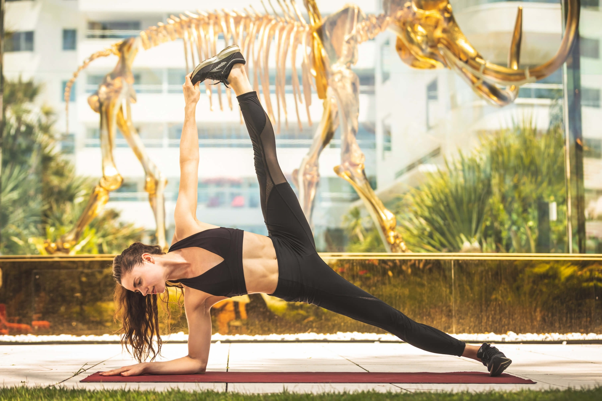 woman wearing black workout gear stretches leg in side plank in front of mammoth skeleton installation