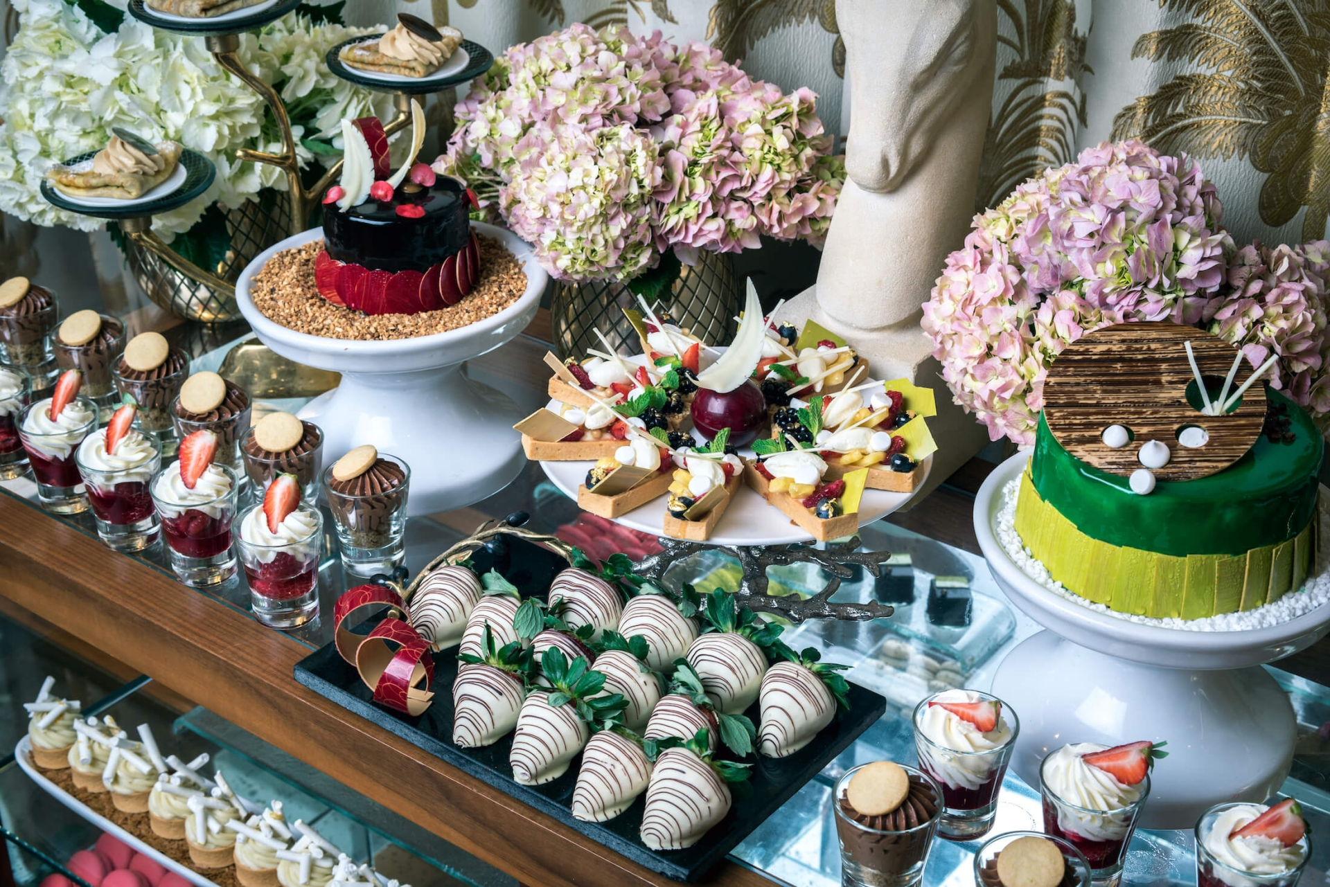 multiple desserts sitting on table surrounded by flowers