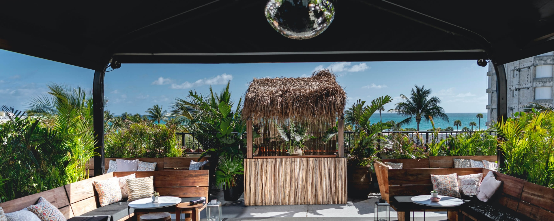 disco ball hangs above open air patio seating area with tiki bar