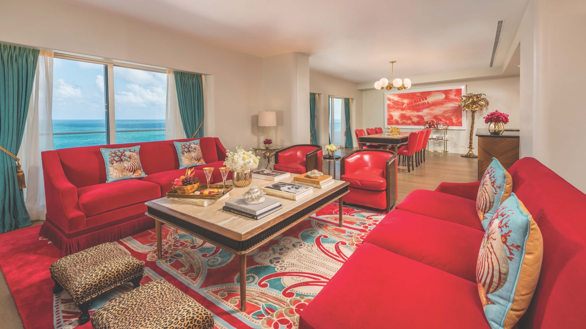 interior of sitting area with red couches, leopard print foot stools and the ocean visible through large window