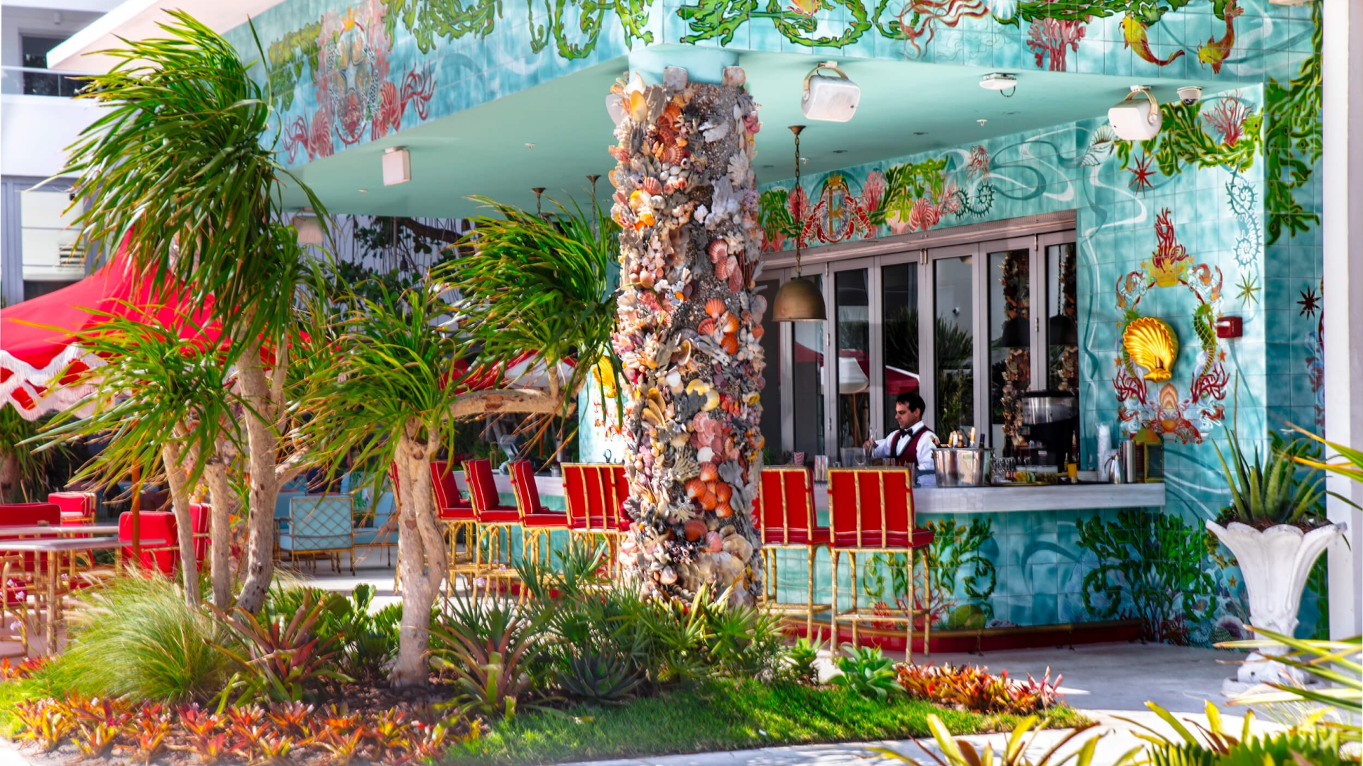image of outdoor bar with bright tree painting and red chairs