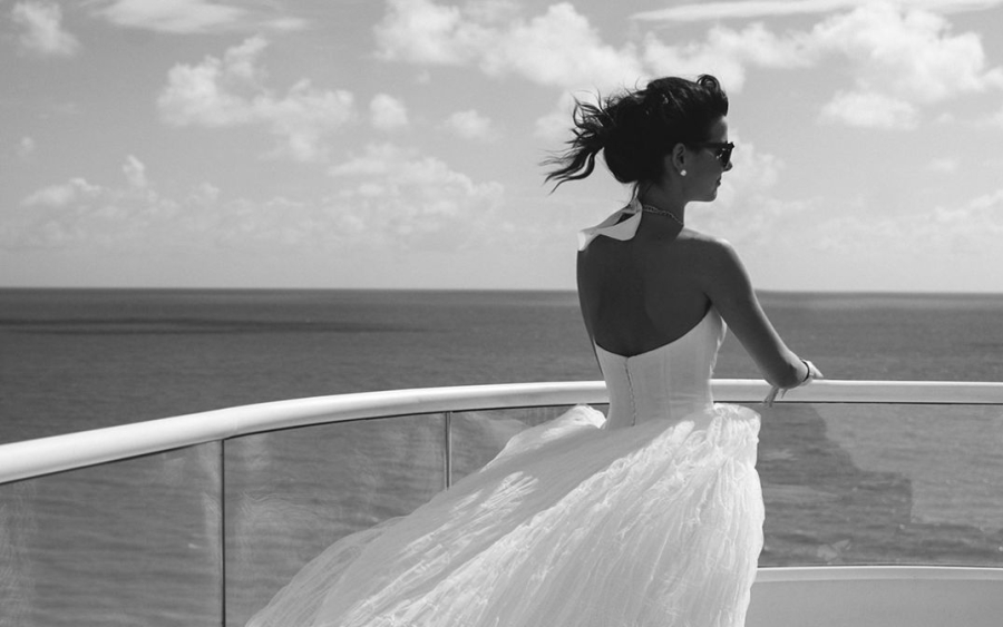 Bride in wedding dress looking out over ocean