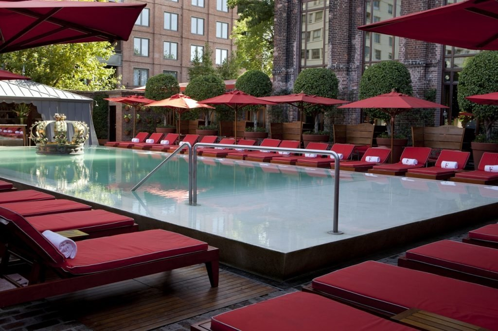 pool surrounded by red lounge chairs