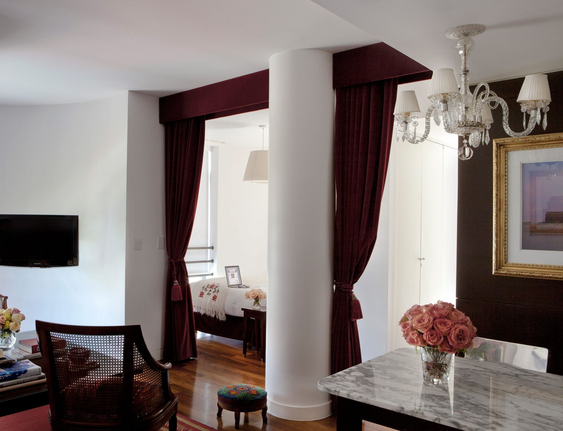 hotel studio room with large column and velvet curtains