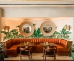 banquette seating dining area with palm leave mural