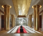 long lobby hallway with six golden columns